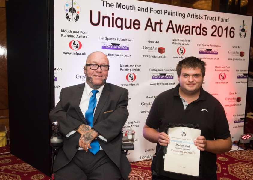Jordan Bell, right, wins the Bronze Award at the Unique Art Awards, with mouth painting artist Steven Chambers. Photo: Max Colson