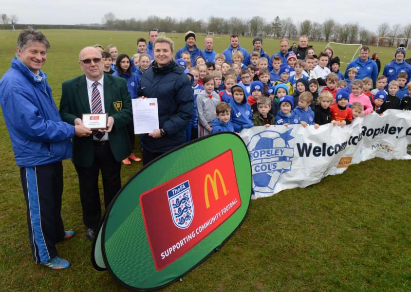 Gary Reeves receives the award on behalf of the club from The FA's Reg Jackson and Sophie Bartup, with Ropsley Colts club members looking on. Photo: Toby Roberts