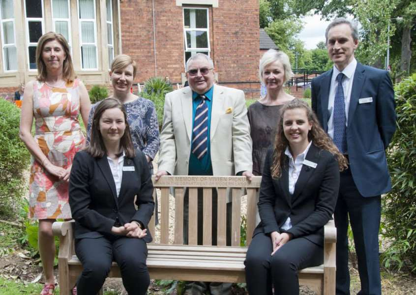 With the memorial bench to former KGGS teacher Viv Pickup are David Pickup (centre) with some of Viv's former colleagues, Eva Kampichler, Judith Kedge, Veronica Hawkins and David Scott. Seated are two of the current Head Girls Niamh Morrissey and Giorgia Bosworth.
