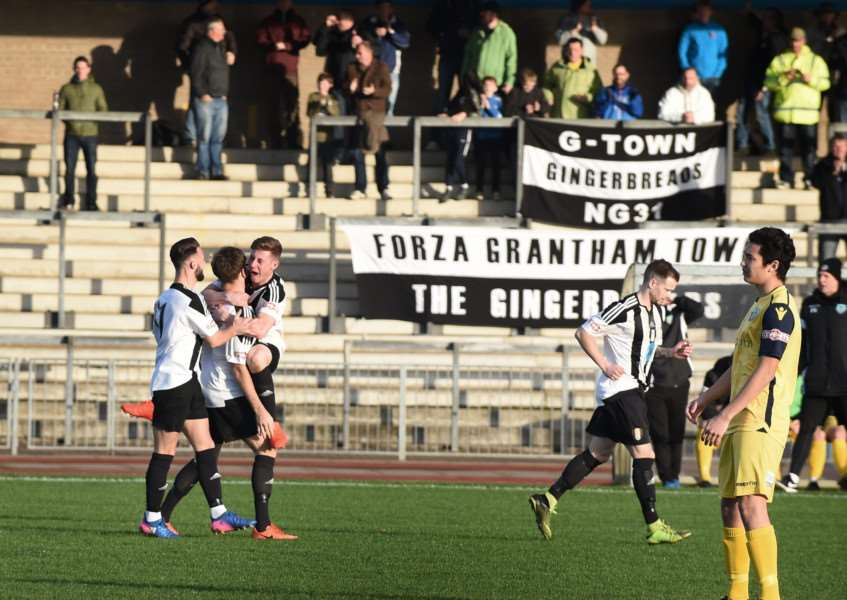 Grantham Town celebrate Jordan Hempenstall's opening goal in front of the jubilant Meres faithful. Photo: Toby Roberts