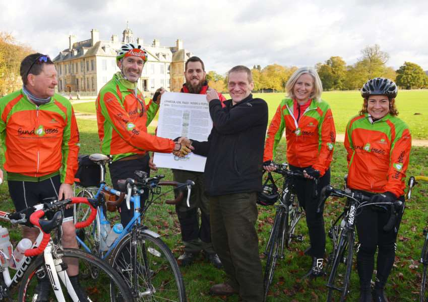 Fund-raising cyclist Gabriel Hemery with Belton House Rangers Nick Brown and Chris Shaw with a copy of the new Tree Charter watched by the rest of the cycling team including Ruth Hyde (second from right) of the Woodland Trust based at their offices on Dysart Road.