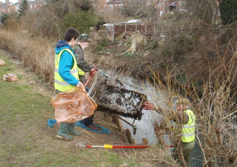 Rivercare volunteers pull a supermarket trolley out of the River Witham.