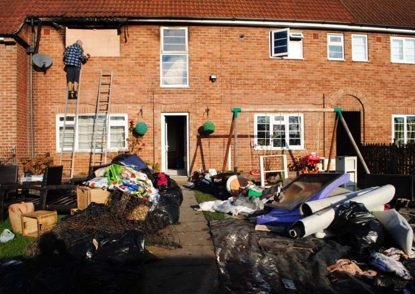 Ruined belongings fill the front garden following the fire at the house in Easthorpe Lane, Redmile.