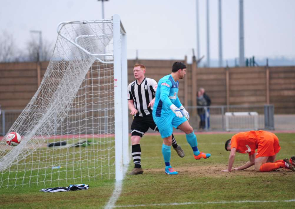 Ben Saunders (centre) gives Grantham Town an early lead on Saturday. Photo: Toby Roberts