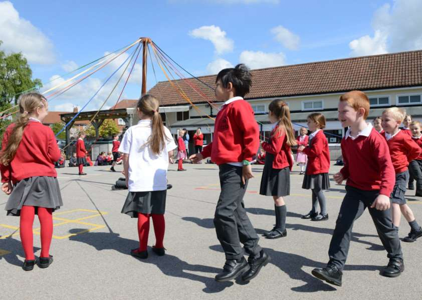 Pupils dance round the maypole at Harrowby Infant School in Grantham.