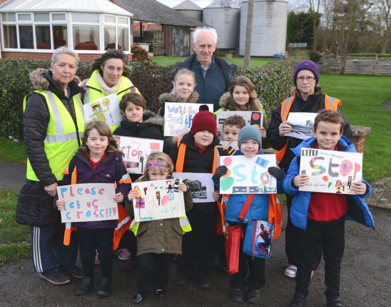 Making their message clear with handmade banners, children and staff from Kings Farm Day Nursery were joined by county councillor Paul Wood during a morning journey across Main Road in Long Bennington this week. Photo: Toby Roberts.