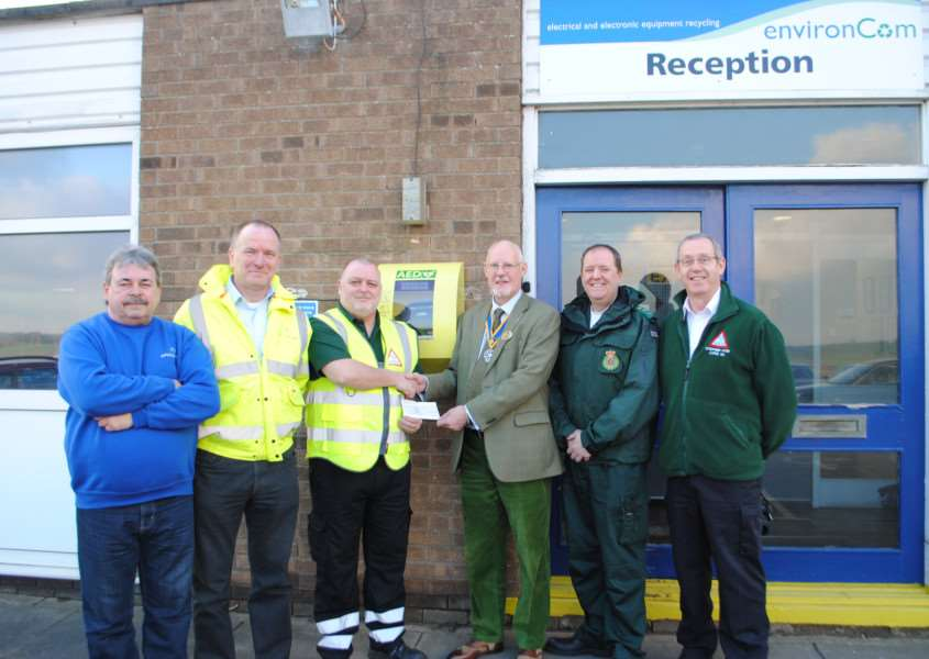 With the new LIVES defibrillator at Environcom in Grantham are, from left, volunteer Phil Upcraft, managing director Cris Stephenson, volunteer Tony Parslow, President of the Rotary Club of Grantham David Burr, EMAS community response manager Steve Pratten and LIVES fund-raising manager Stephen Hyde.