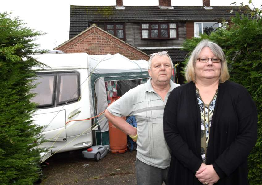 Russell and Sue Winter, who have been living in the pictured caravan since the flooding in August. Photo: Toby Roberts.