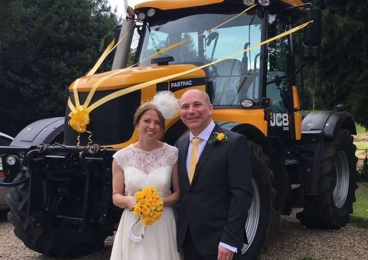 Ruth and Peter with the yellow JCB Fastrac tractor which she drove them to their wedding reception in EMN-160720-103906001