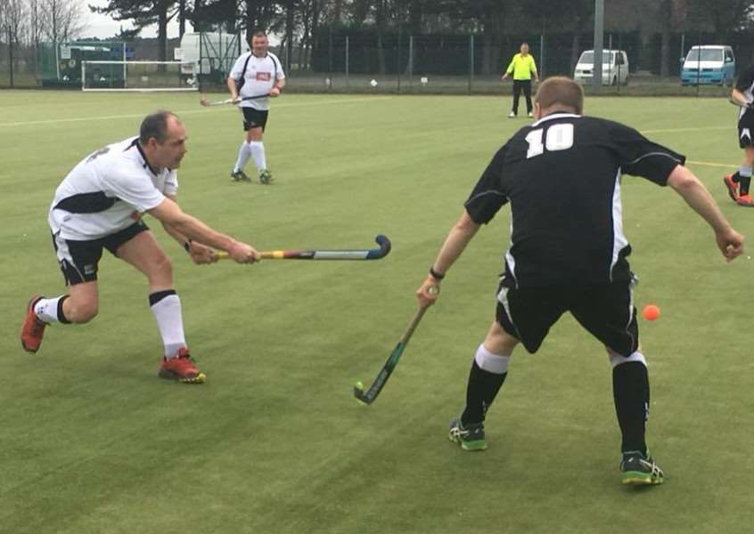Leadenham Hockey Club third team captain Andy Cade (left) clears his lines under pressure from veteran forward James Ireland.