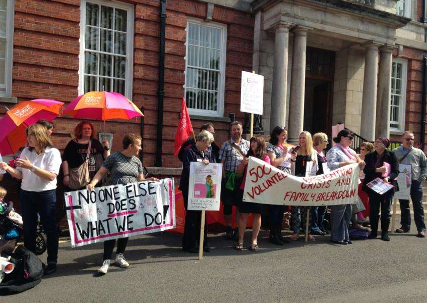 Home-Start volunteers and families demonstrate outside Lincolnshire County Council.