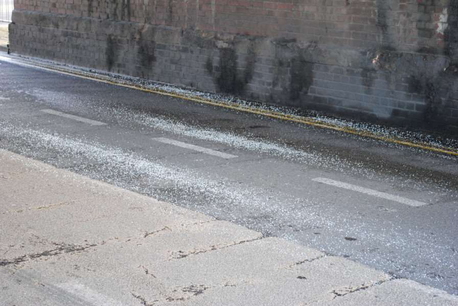 Broken glass remains on the road after the school bus crash at Harlaxton Road rail bridge, Grantham.