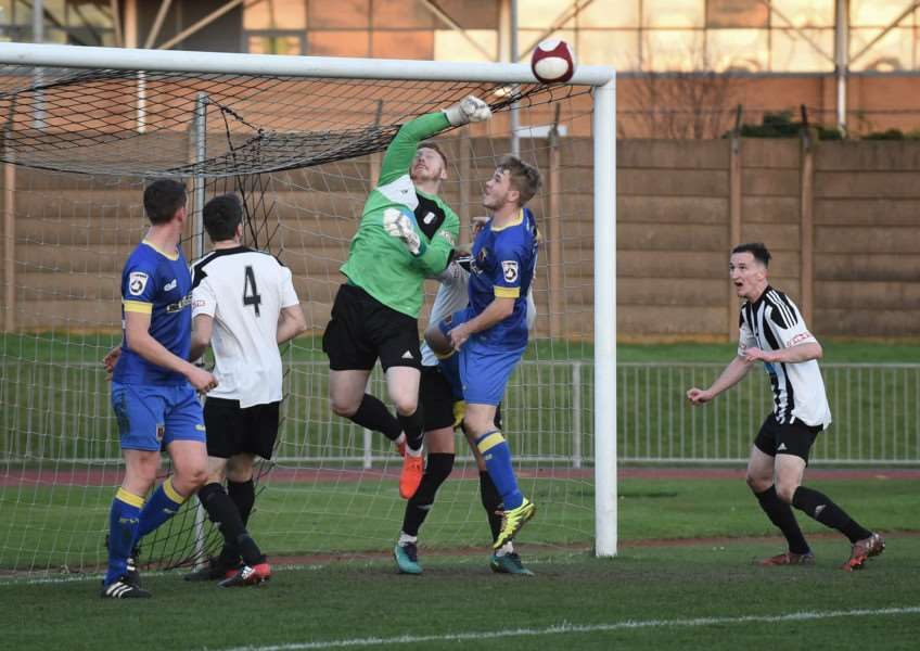 Grantham Town keeper Kieran Preston punches a corner kick from danger. Photo: Toby Roberts