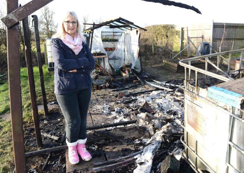 Joy Wilson at her burnt out allotments, where she had been growing produce for the local hospice. Photo: Toby Roberts.