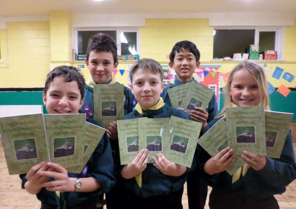 Barrowby Scouts pose with the anthology of their writing created with the help of a local children's author.