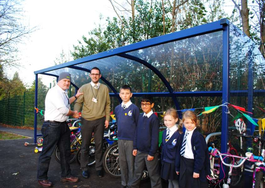 Dr Bike Jon Moody, left, shakes hands with Deputy headteacher David Nicholson after the opening of the new bike shelter at St Mary's Primary School in Grantham. They are joined by pupils.