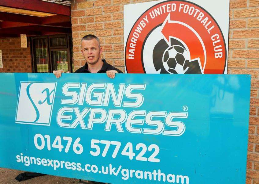 Signs Express owner Ian Charles and his advertising board at the Environcom Stadium.