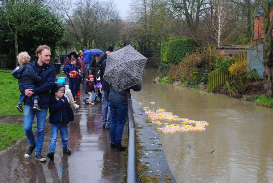 Spectators protect themselves from the downpour as the ducks come down the Witham.