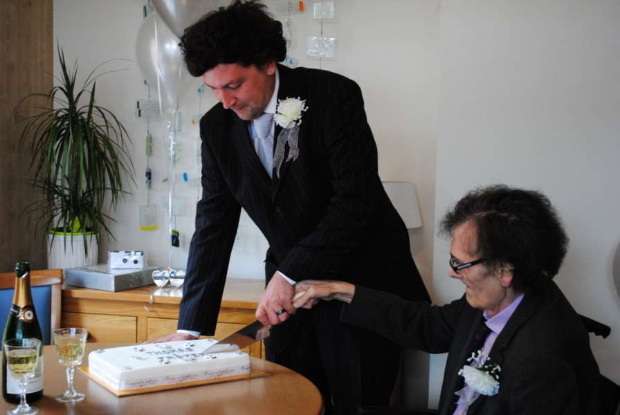 Frazer and Tom cut the cake together.