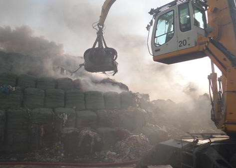 Moving bales away from the fire at Barkston Heath this morning. Photo: Phillip Grimes EMN-151007-092832001