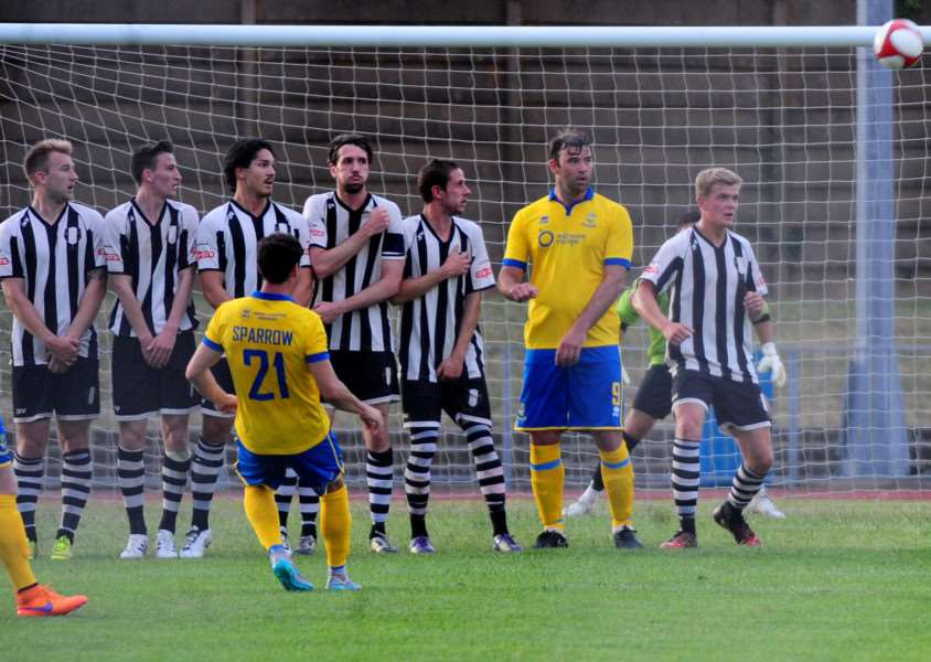 Grantham Town's wall look on as Lincoln's Matt Sparrow curls a free kick goalward. Photo: Toby Roberts