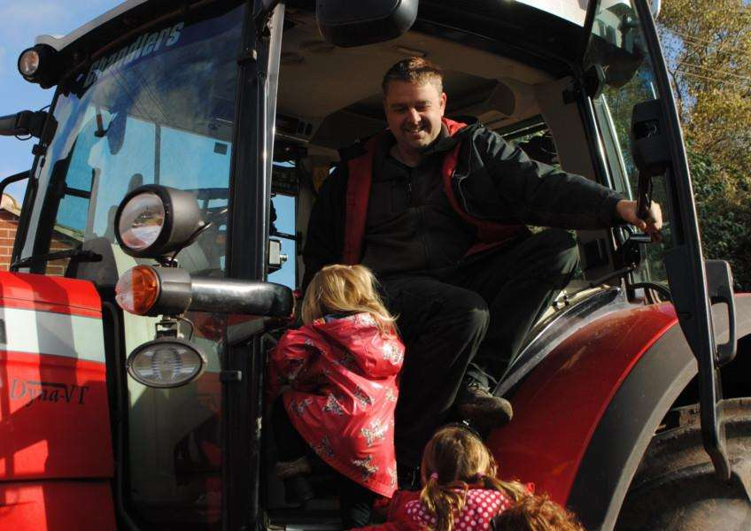 The pre-school children took it turns to sit in the tractor.