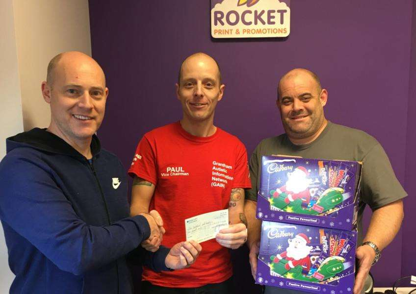 Paul Fixter, of GAIN, receives a donation of money and chocolate selection boxes from Noel Reeves and Chris Reeves at Rocket print and Promotions