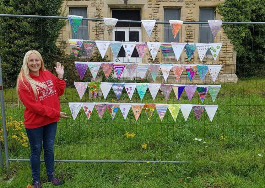 Jody Clark with the artwork sent in by schoolchildren to be displayed outside the old hospital in Manthorpe Road.