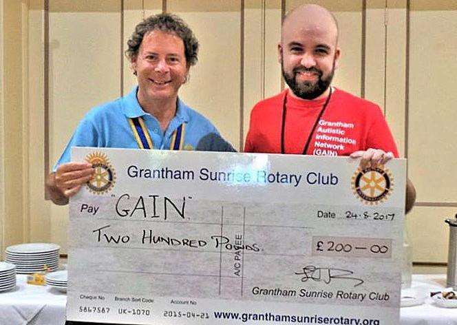 Grantham Sunrise Rotary president Lez Jones presents a cheque to GAIN's Edward Mayes.