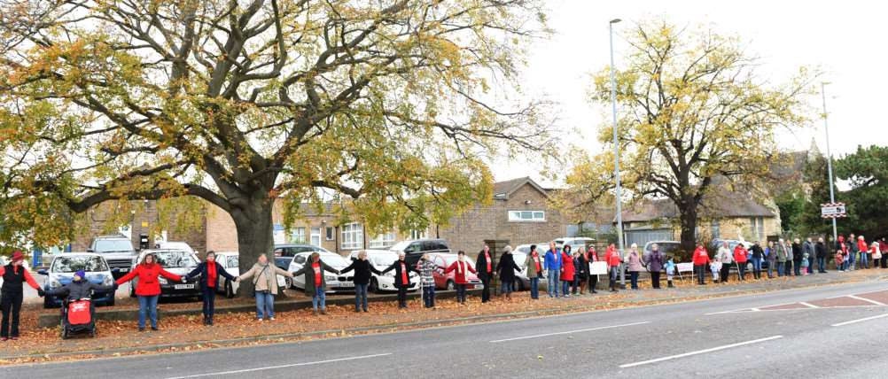 People hold hands as they protest outside Grantham Hospital.