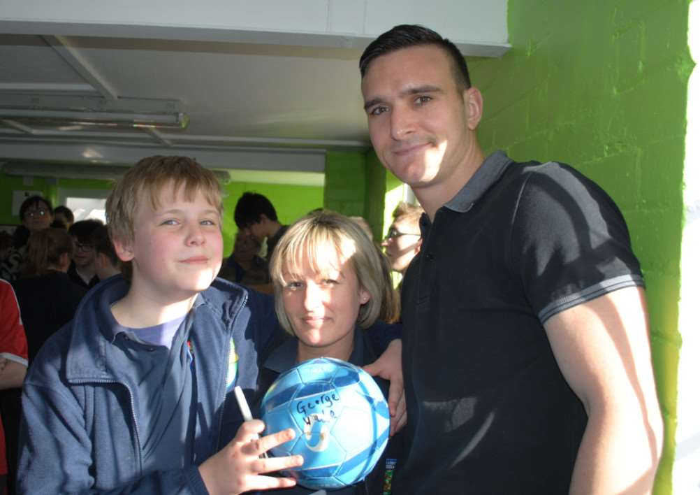 Nottingham Forest player Jack Hobbs signs Ambergate pupil George Wade's football with teacher Claire White, centre. Photo: 0310B