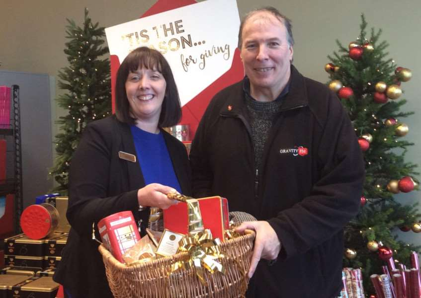 Jeanette Portman, of Grantham M&S, donates a Christmas hamper to Ian Selby as a prize for the A&E poetry competition.