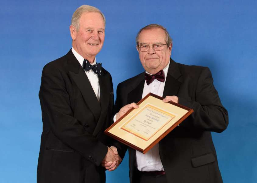 Roy Wright is presented with his honorary membership by Air Chief Marshal Sir Michael Alcock.