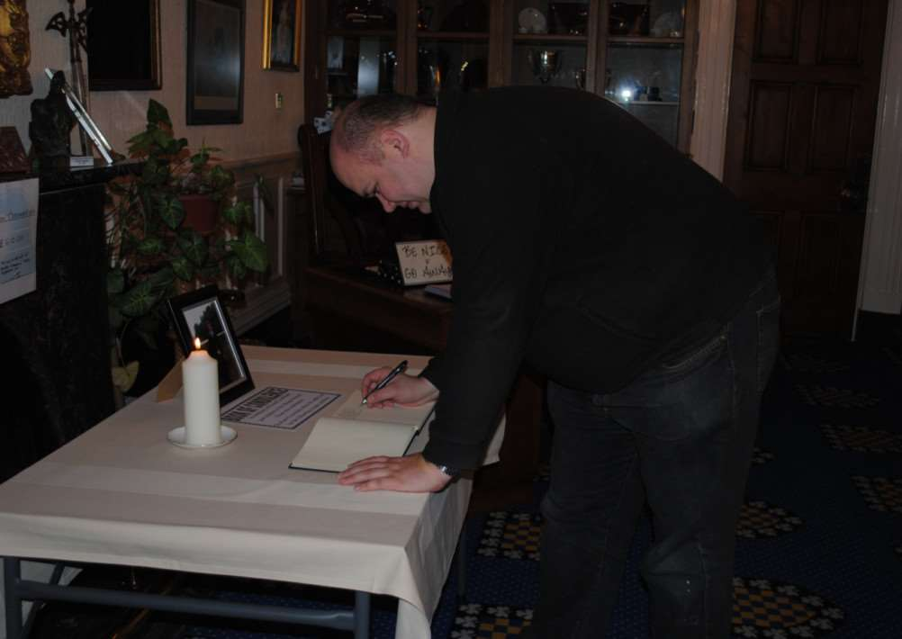 Doug Hough signs the book of condolence for Euan Coulthard.