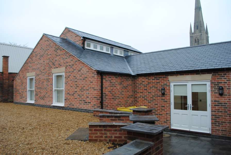 An exterior view of the new extension to the Vine House Surgery with St Wulfram's Church in the background.