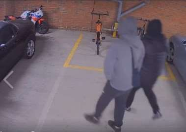 CCTV shows the two suspects approaching the Honda motorcycle belonging to Lawrence Banks.