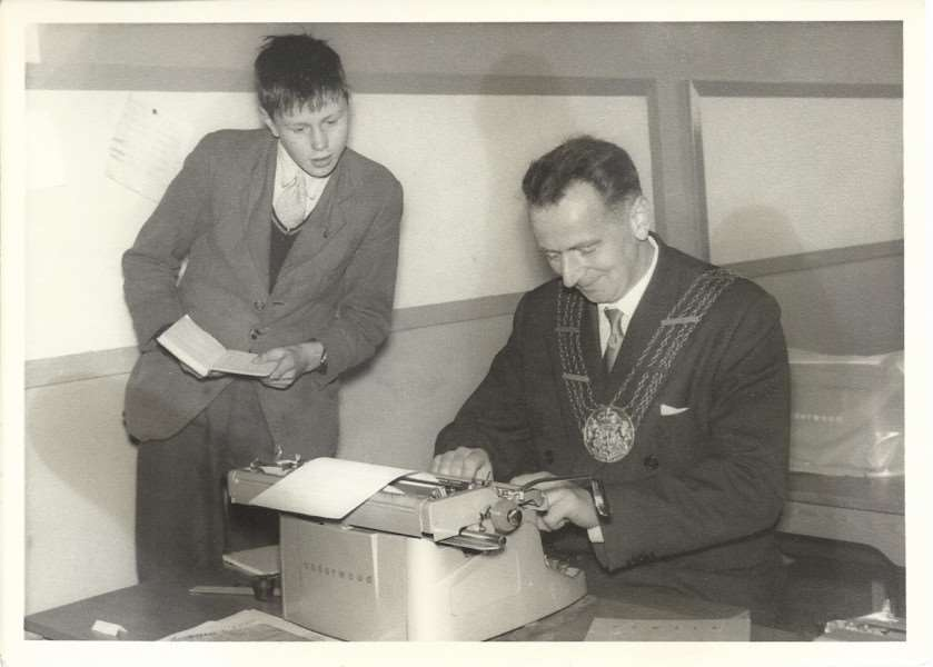Mayor of Grantham Fred Foster in a typing pool. Who is the boy watching him?