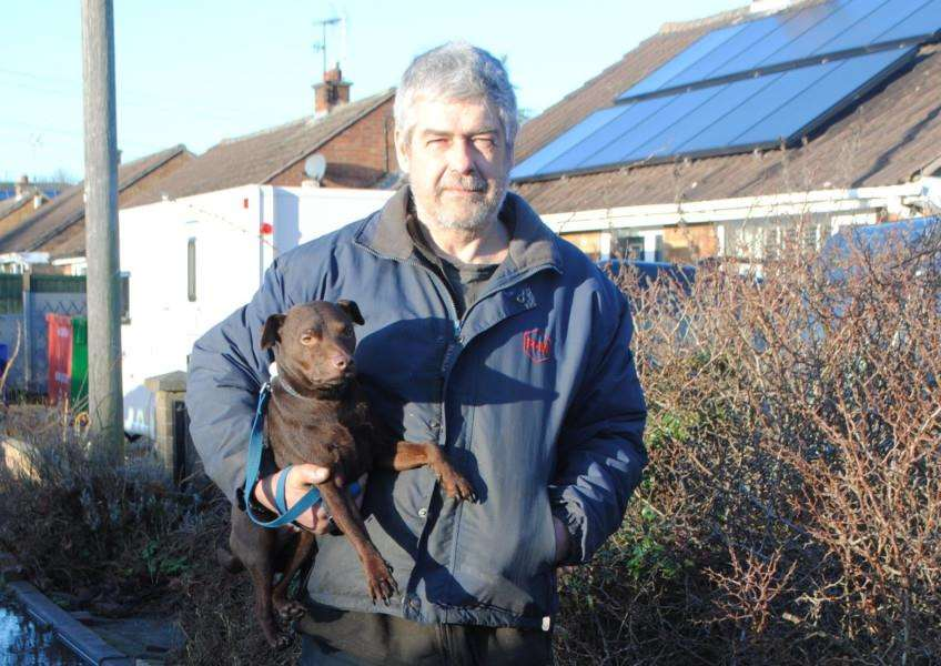 Dave Oliver, pictured with his dog Eddie, is fed up of the flooding outside his home on Harlaxton Road.