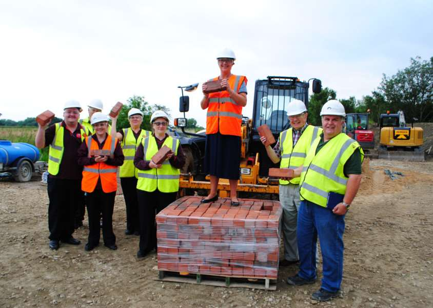 Debbie Wrightson, manager of Sainsbury's in Grantham, holds one of the important bricks which will be part of the restoration of lock 15 on Grantham Canal. She is pictured with Sainsbury's staff and canal volunteers. EMN-160727-195414001