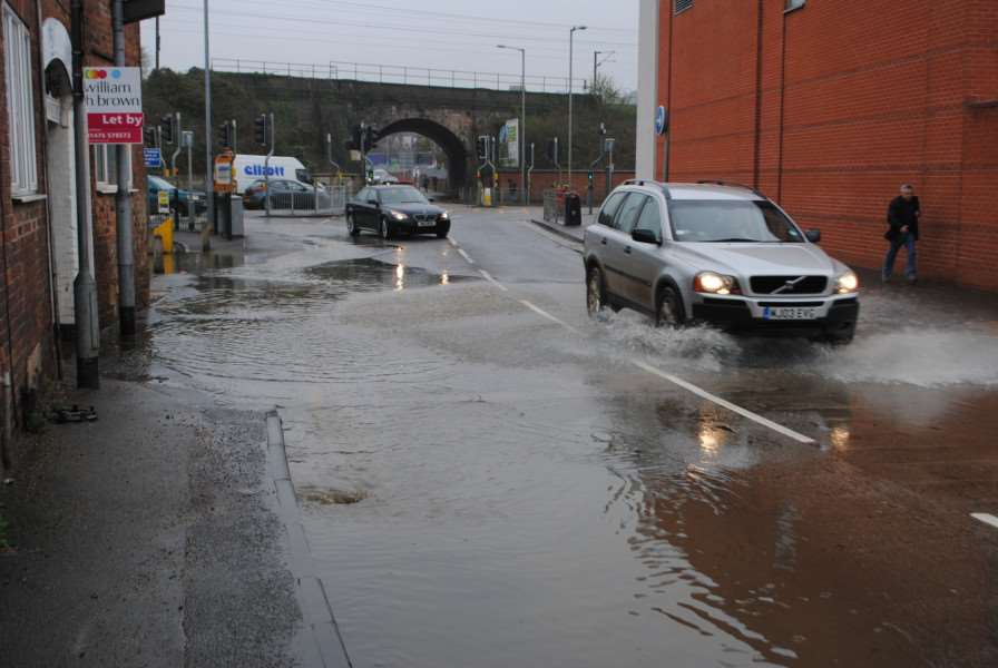 Water floods Dysart Road after a water main burst.