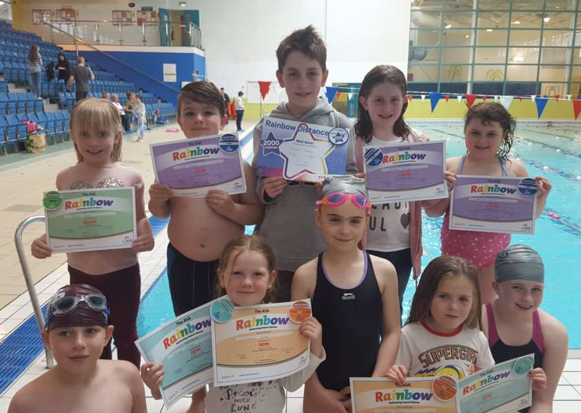 Swim School members show off their distance certificates.