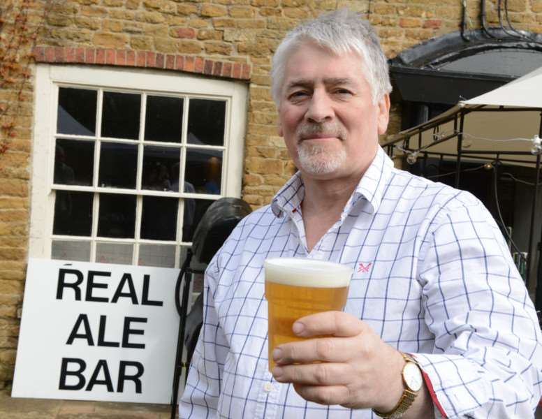 Ian Pollock, new landlord of the Welby Arms in Denton, offers some refreshment at Denton Street Market.