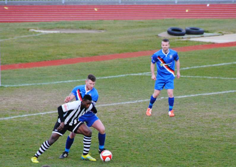 Grantham Town's Lee Ndlovu comes under pressure in the Whitby 18-yard box. Photo: John Burgess