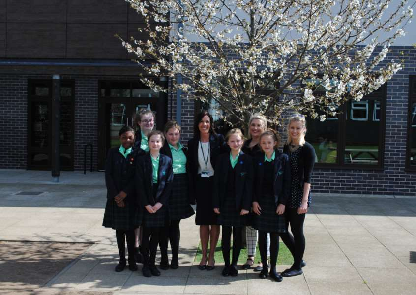 Caroline Saxelby surrounded by students at Walton Girls' High School and Sixth Form.