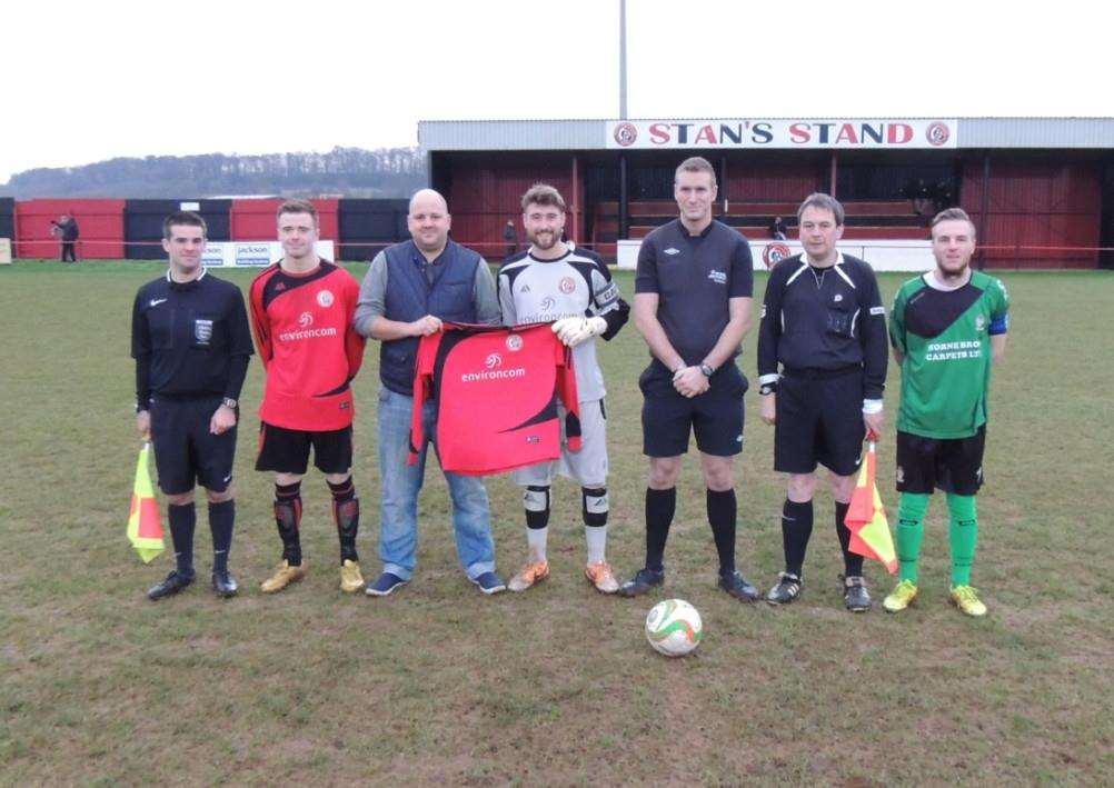 Harrowby United man-of-the-match Liam Motson and Indulgence Delivered's Martin Richards receiving a replica shirt as match sponsor for the game, with the officials, team captains Jack Drury and Sleaford's Scott Coupland.