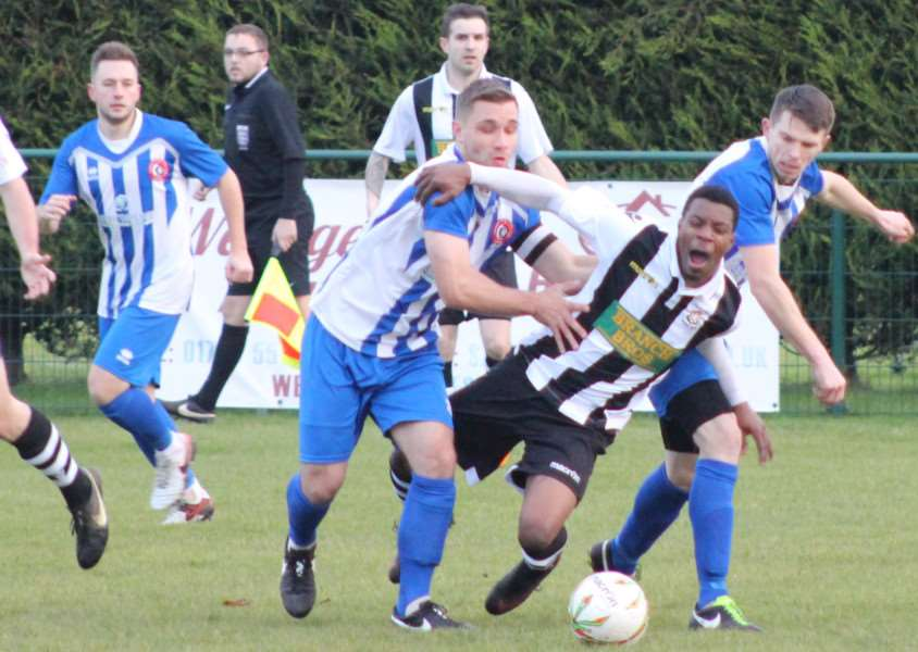 Harrowby's John Currall and Simon Bolland crowd out PNS striker Jezz Goldson-Williams, with Tom Parker looking on.