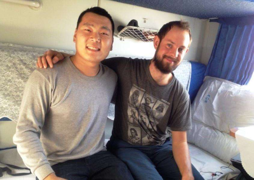 Nick Thomson with a new friend on a train travelling through China.