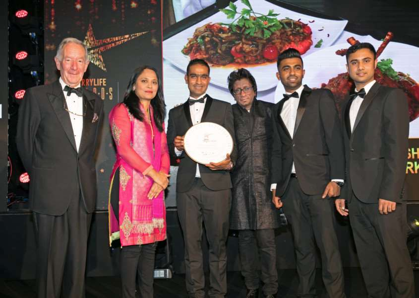 The Ashiana won two awards at the Curry Life Awards. Pictured from left are host Michael Buerk, Rushanara Ali MP, Ashiana owner Saiqul Miah (holding plate), Illy Jaffar from Chivas, Jay Miah and chef Sujon Miah. Photo: Kois Miah