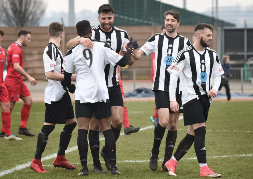Grantham Town players congratulate number nine Zayne Hakeem on his opening goal at The Meres on Saturday. Photo: Toby Roberts