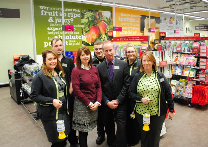 Tina Dingley, of Grantham Hospice, and M&S store manager Dean Law with staff.